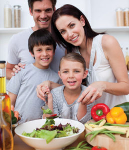 Young  mother cooking vegetables in kitchen with her family