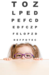 Funny girl in eyeglasses with eye chart behind